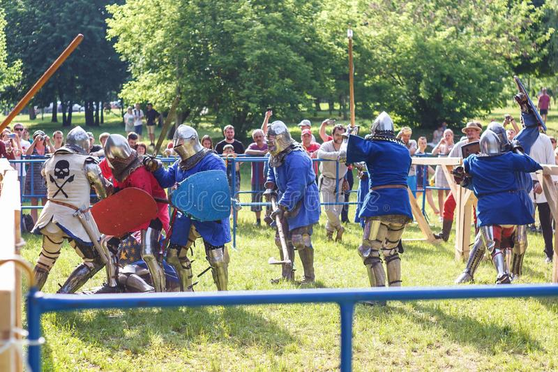 GRODNO, BELARUS - JUNE 2019: group of medieval jousting knight fight, in armor, helmets, chain mail with axes and swords on lists. Historic reconstruction of royalty free stock image