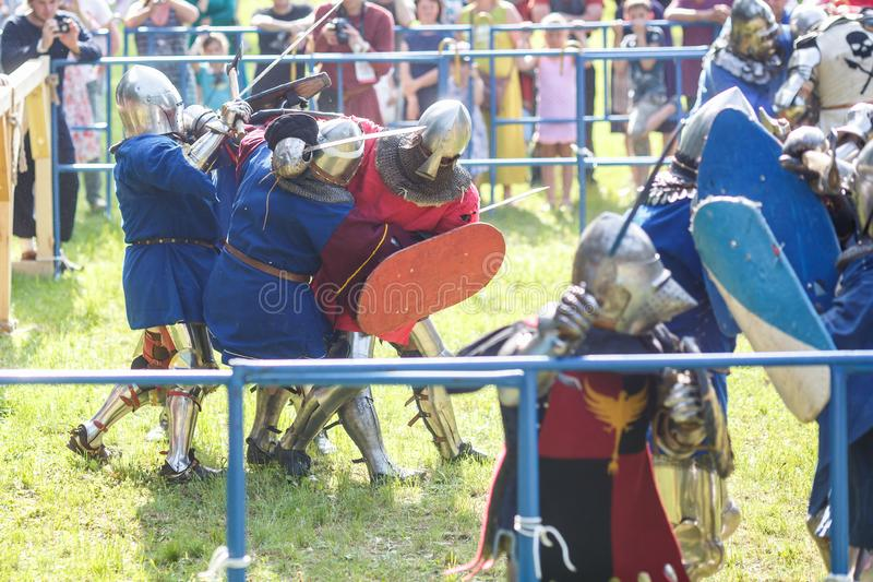 GRODNO, BELARUS - JUNE 2019: group of medieval jousting knight fight, in armor, helmets, chain mail with axes and swords on lists. Historic reconstruction of royalty free stock photography
