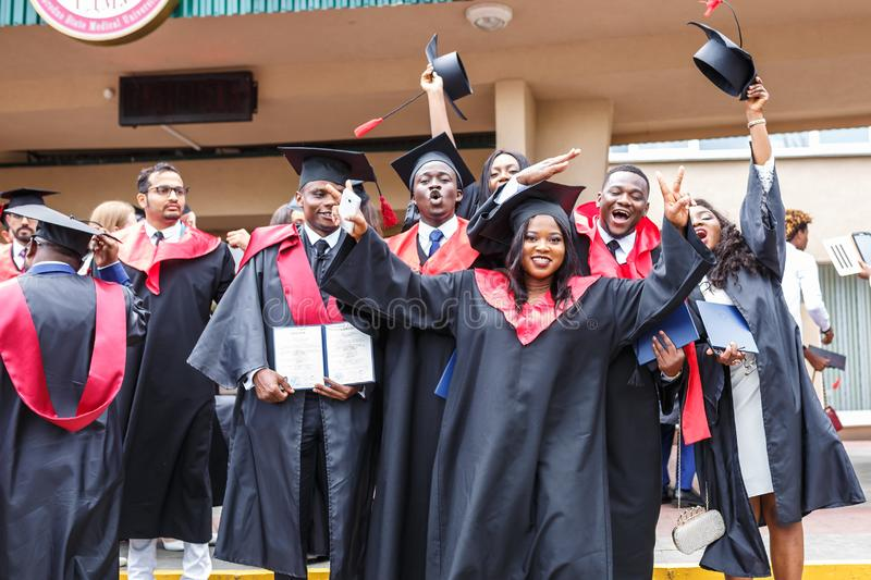 GRODNO, BELARUS - JUNE, 2018: Happy foreign african medical students in square academic graduation caps and black raincoats during royalty free stock photography