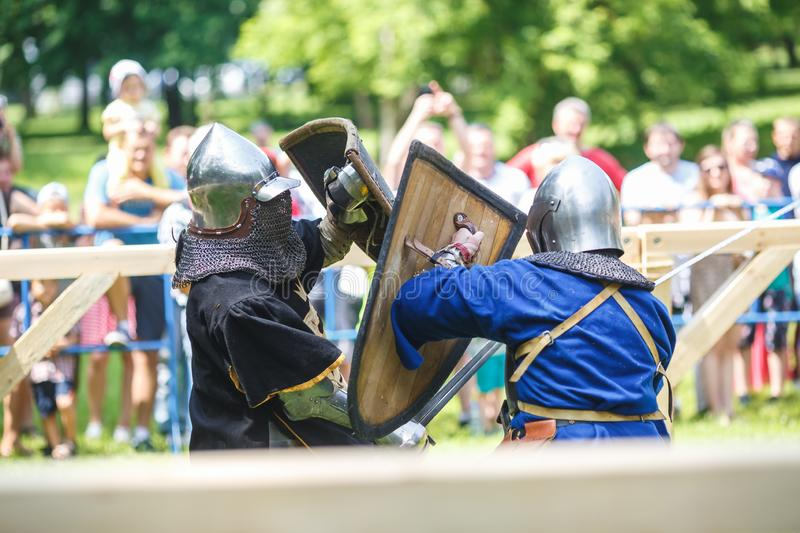 GRODNO, BELARUS - JUNE 2019: medieval jousting knight fight, in armor, helmets, chain mail with axes and swords on lists. historic. Reconstruction of ancient stock image