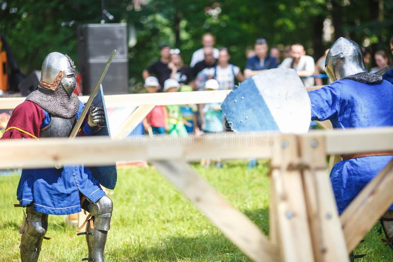 GRODNO, BELARUS - JUNE 2019: medieval jousting knight fight, in armor, helmets, chain mail with axes and swords on lists. historic. Reconstruction of ancient stock images