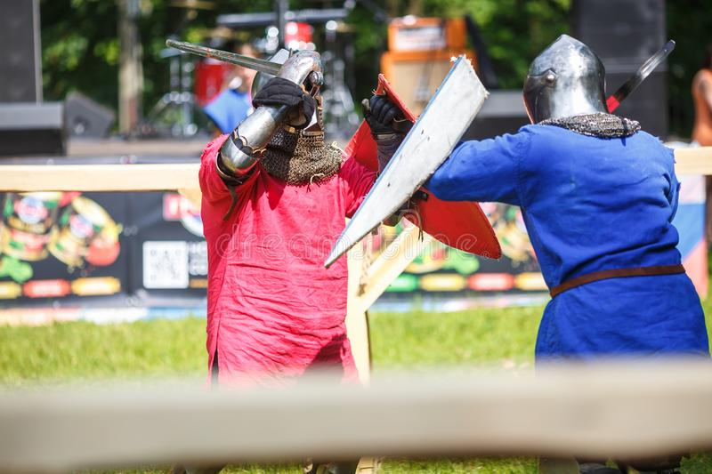 GRODNO, BELARUS - JUNE 2019: medieval jousting knight fight, in armor, helmets, chain mail with axes and swords on lists. historic. Reconstruction of ancient stock photography