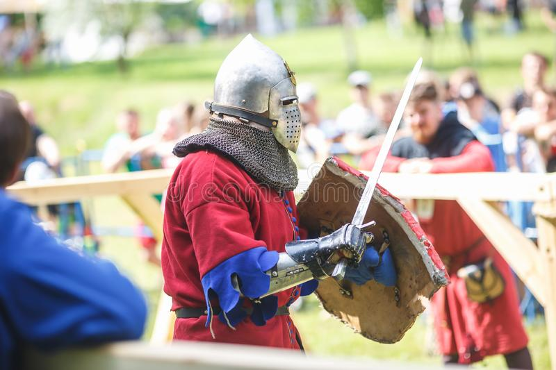 GRODNO, BELARUS - JUNE 2019: medieval jousting knight fight, in armor, helmets, chain mail with axes and swords on lists. historic. Reconstruction of ancient royalty free stock images