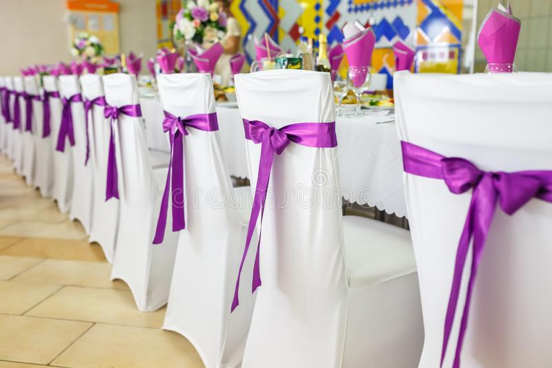 GRODNO, BELARUS - MAY 2014: Beautiful flowers on elegant dinner table in wedding day. Decorations served on the festive table in. Violet background stock photos