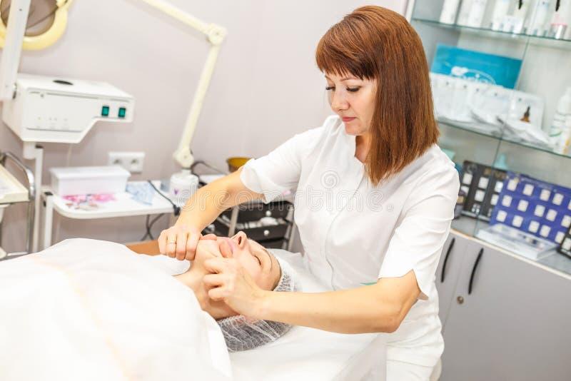 GRODNO BIAŁORUŚ, MAJ, - 2018: kobieta robi twarzowemu masażowi przy piękno salonem obraz royalty free