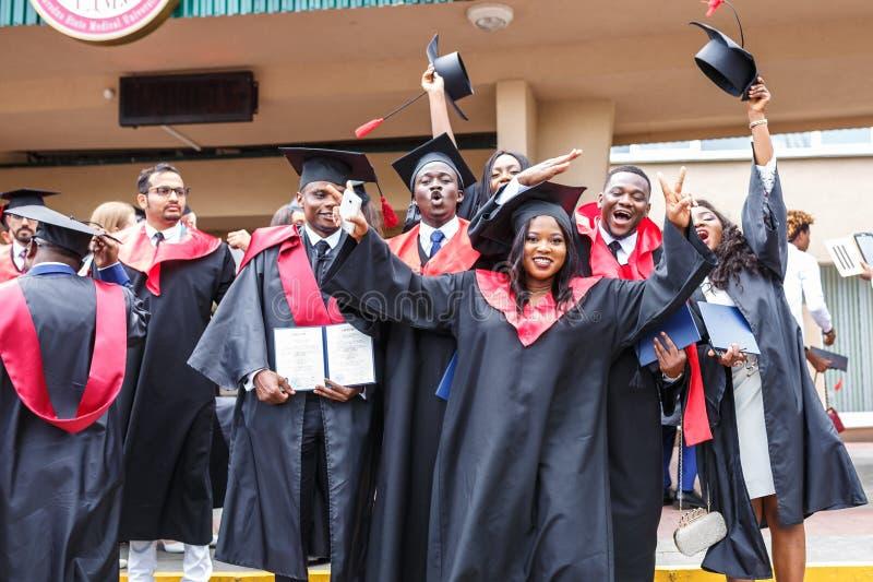 GRODNO, BIELORRÚSSIA - EM JUNHO DE 2018: Estudantes de Medicina africanas estrangeiras felizes em tampões acadêmicos quadrados da fotografia de stock royalty free