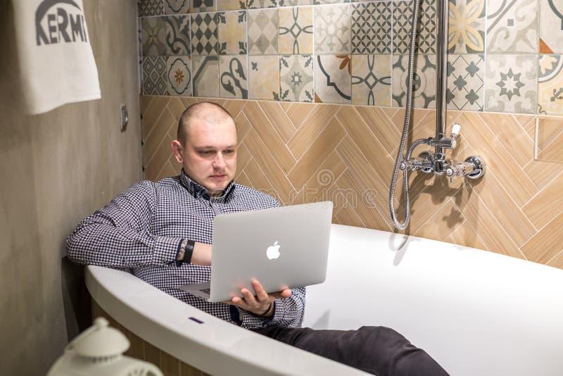 GRODNO, BIELORRÚSSIA - EM MARÇO DE 2019: os empregados do homem novo colocam no banho com o laptop na loja sondando luxuosa moder fotografia de stock royalty free