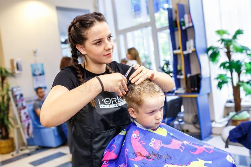 GRODNO, BIELORRUSIA - MAYO DE 2016: coiffeur principal del peluquero que hace un peinado en el sal?n del peluquero para el peque? foto de archivo