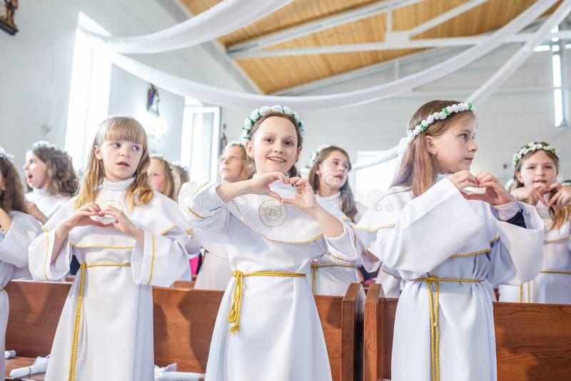 GRODNO, BIELORUSSIA - MAGGIO 2019: I bambini piccoli nella chiesa cattolica stanno aspettando la prima comunione del eucharist Pi immagini stock libere da diritti