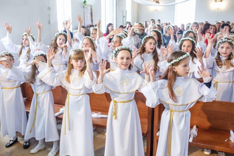 GRODNO, BIELORUSSIA - MAGGIO 2019: I bambini piccoli nella chiesa cattolica stanno aspettando la prima comunione del eucharist Pi fotografie stock
