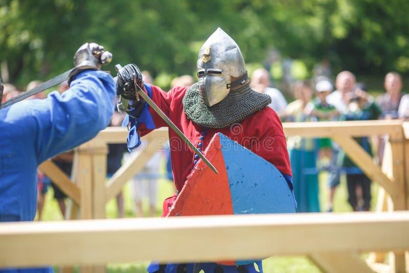 GRODNO VITRYSSLAND - JUNI 2019: medeltida jousting riddarekamp, i harnesk, hjälmar, ringbrynja med yxor och svärd på listor histo arkivbilder