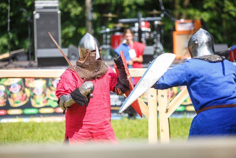 GRODNO VITRYSSLAND - JUNI 2019: medeltida jousting riddarekamp, i harnesk, hjälmar, ringbrynja med yxor och svärd på listor histo royaltyfria foton