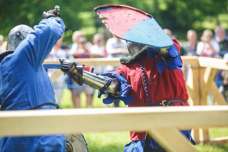 GRODNO VITRYSSLAND - JUNI 2019: medeltida jousting riddarekamp, i harnesk, hjälmar, ringbrynja med yxor och svärd på listor histo arkivbild