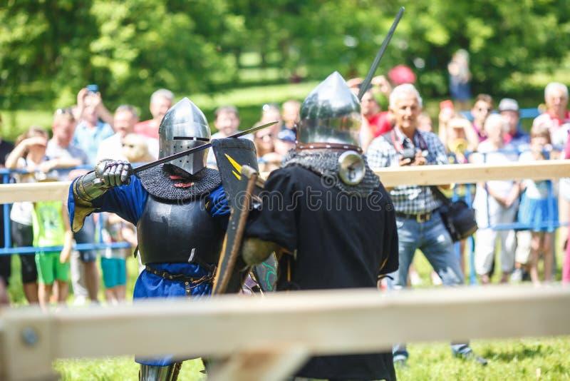 GRODNO VITRYSSLAND - JUNI 2019: medeltida jousting riddarekamp, i harnesk, hjälmar, ringbrynja med yxor och svärd på listor histo arkivfoto