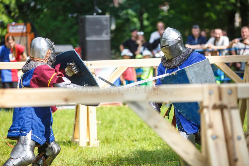 GRODNO VITRYSSLAND - JUNI 2019: medeltida jousting riddarekamp, i harnesk, hjälmar, ringbrynja med yxor och svärd på listor histo royaltyfri bild