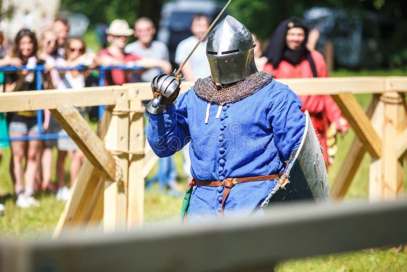 GRODNO VITRYSSLAND - JUNI 2019: medeltida jousting riddarekamp, i harnesk, hjälmar, ringbrynja med yxor och svärd på listor histo royaltyfri fotografi