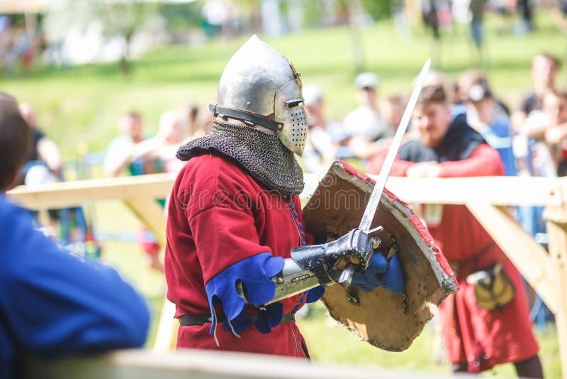 GRODNO VITRYSSLAND - JUNI 2019: medeltida jousting riddarekamp, i harnesk, hjälmar, ringbrynja med yxor och svärd på listor histo royaltyfria bilder