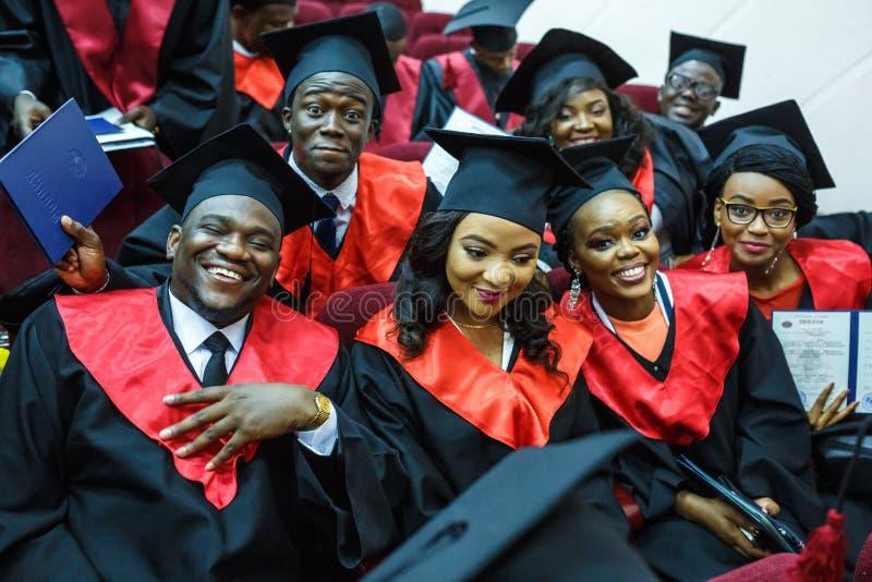 GRODNO VITRYSSLAND - JUNI, 2018: Utländska afrikanska medicinare i fyrkantiga akademiska avläggande av examenlock och svarta regn royaltyfri bild