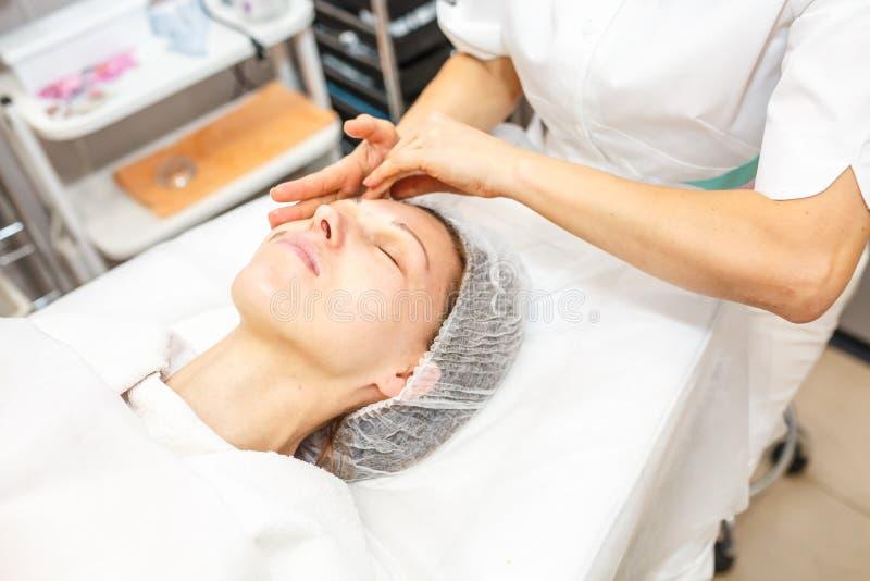 GRODNO VITRYSSLAND - MAJ 2018: kvinna som gör ansikts- massage på skönhetsalongen arkivfoto