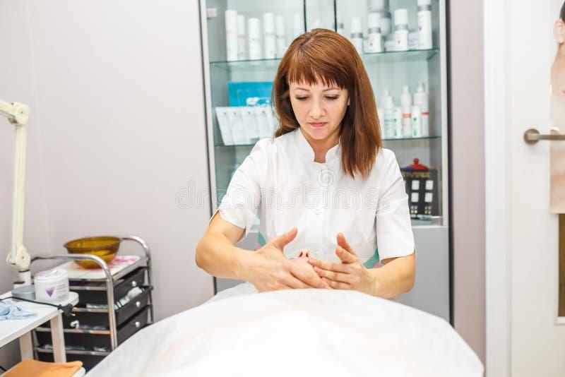 GRODNO VITRYSSLAND - MAJ 2018: kvinna som gör ansikts- massage på skönhetsalongen royaltyfri bild