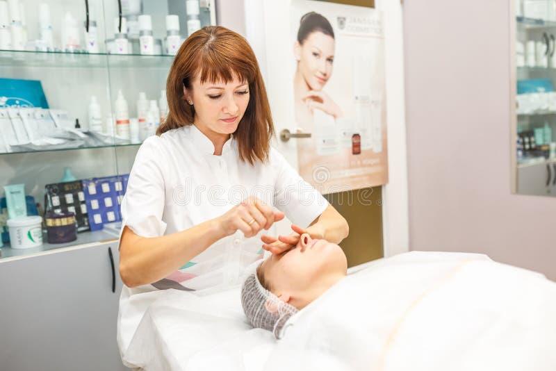 GRODNO VITRYSSLAND - MAJ 2018: kvinna som gör ansikts- massage på skönhetsalongen arkivfoton