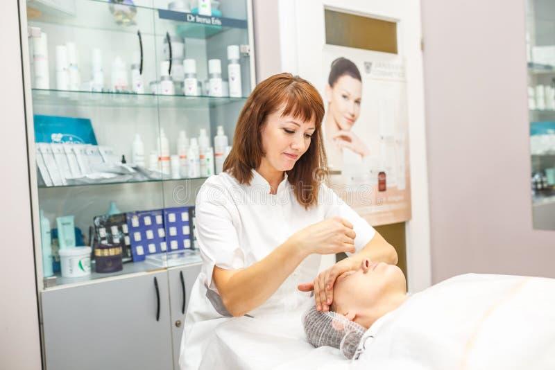 GRODNO VITRYSSLAND - MAJ 2018: kvinna som gör ansikts- massage på skönhetsalongen royaltyfria bilder