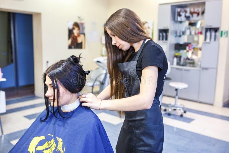 GRODNO, WEISSRUSSLAND - MAI 2016: Vorlagenfriseur Coiffeur, der eine Frisur im Friseursalon für junge Frau tut lizenzfreie stockbilder