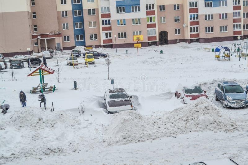 Grodno, Wit-Rusland, 12 15 2012 is Er heel wat sneeuw in de werf van het flatgebouw, het vriendschappelijke schoonmaken van de sn stock afbeelding