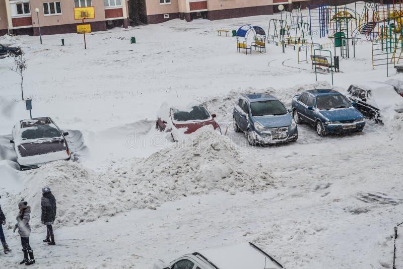 Grodno, Wit-Rusland, 12 15 2012 is Er heel wat sneeuw in de werf van het flatgebouw, het vriendschappelijke schoonmaken langs van royalty-vrije stock fotografie