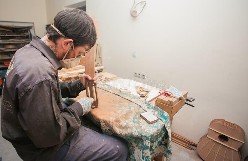 GRODNO, WIT-RUSLAND - JANUARI 18, 2017 Ernstige professionele gitaar-maker die met onvolledige gitaar op workshop werken royalty-vrije stock foto's