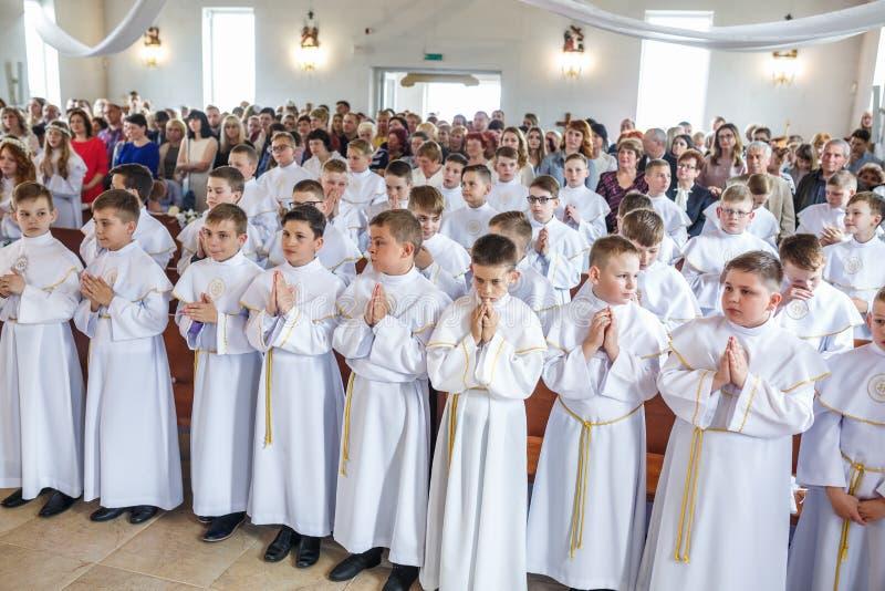 GRODNO, WIT-RUSLAND - MEI 2019: De jonge kinderen in de Katholieke Kerk wachten op de eerste eucharistkerkgemeenschap Kleine enge stock foto