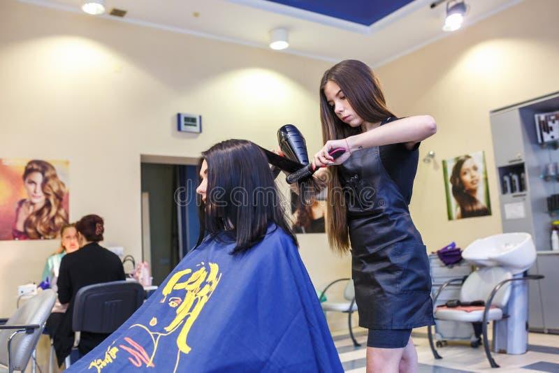 GRODNO, WIT-RUSLAND - MEI 2016: hoofdkappercoiffeur die een kapsel in kapperssalon doen voor jonge vrouw stock afbeeldingen