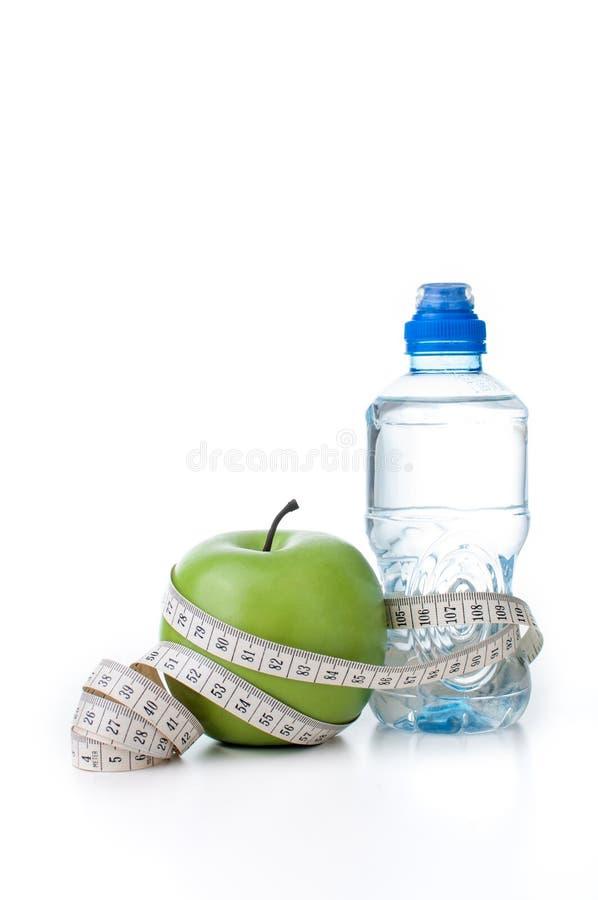 Groen appel en flessenwater met het meten van band stock afbeeldingen
