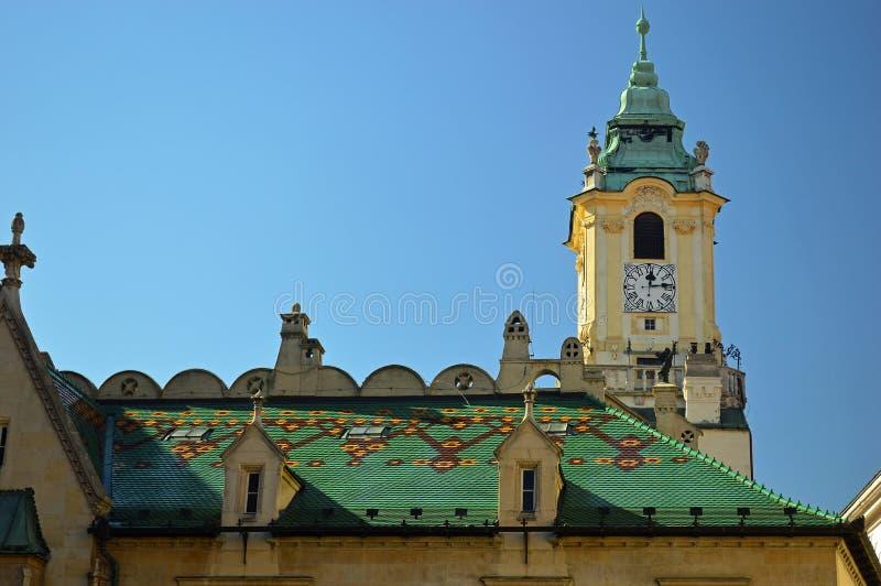 Groen betegeld dak met stadhuisklokketoren achter Bratislava stock foto