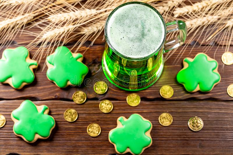 Groen bier in een glasmok met peperkoekklaver, hoef, tarweaar en gouden muntstukken op een rustieke houten oppervlakte feestelijk stock foto