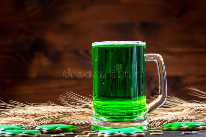 Groen bier in een glasmok met peperkoekklaver, hoef, tarweaar en gouden muntstukken op een rustieke houten oppervlakte feestelijk stock afbeeldingen