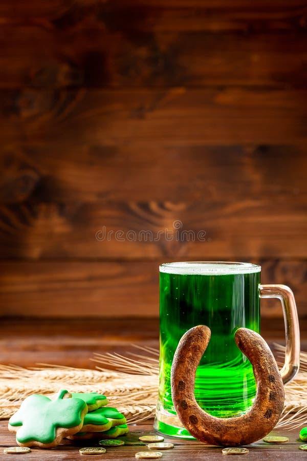 Groen bier in een glasmok met peperkoekklaver, hoefijzer en gouden muntstukken op een rustieke houten oppervlakte Feestelijke ach royalty-vrije stock afbeeldingen