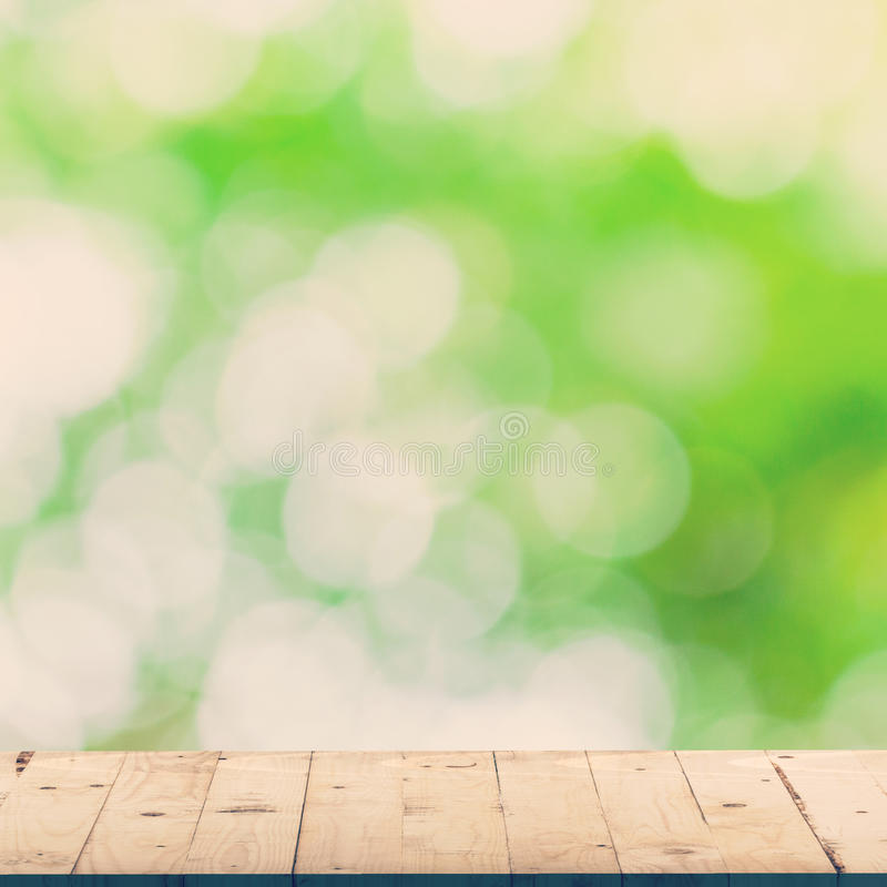 Groen blad bokeh onduidelijk beeld en houten lijst stock fotografie