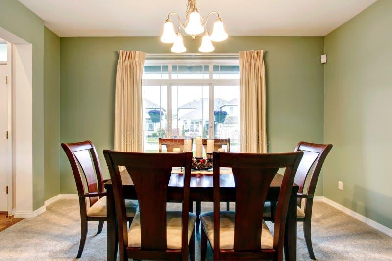 Groen eetkamerbinnenland met klassiek bruin meubilair. royalty-vrije stock afbeelding