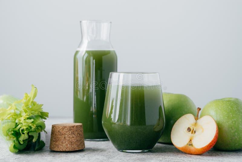 Groen gezond selderie en appelsap in glaswerk Plantaardige drank Verse smoothie over witte achtergrond organisch royalty-vrije stock afbeeldingen