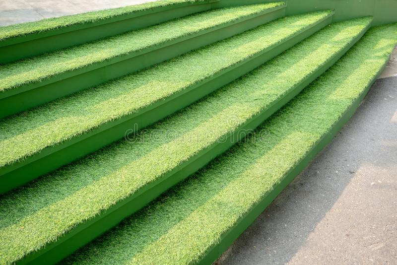 Groen gras op concrete treden voor de decoratieconcept van het aardthema stock afbeeldingen
