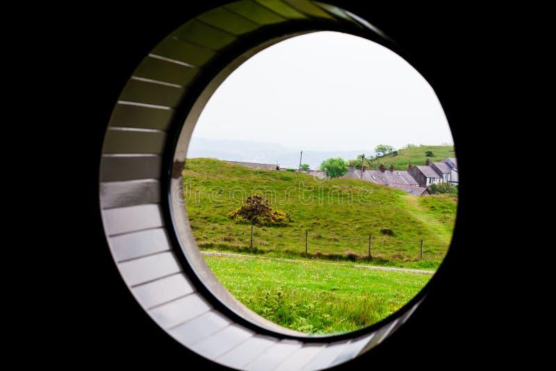 Groen gras op het weidegebied met overzees op de achtergrond Samenstelling door het ronde venster Mooie landschapssamenstelling stock afbeeldingen