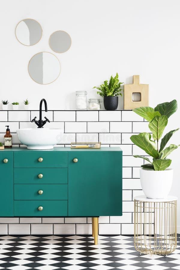 Groen kabinet naast installatie op gouden lijst in modern badkamersbinnenland met spiegels Echte foto royalty-vrije stock afbeeldingen