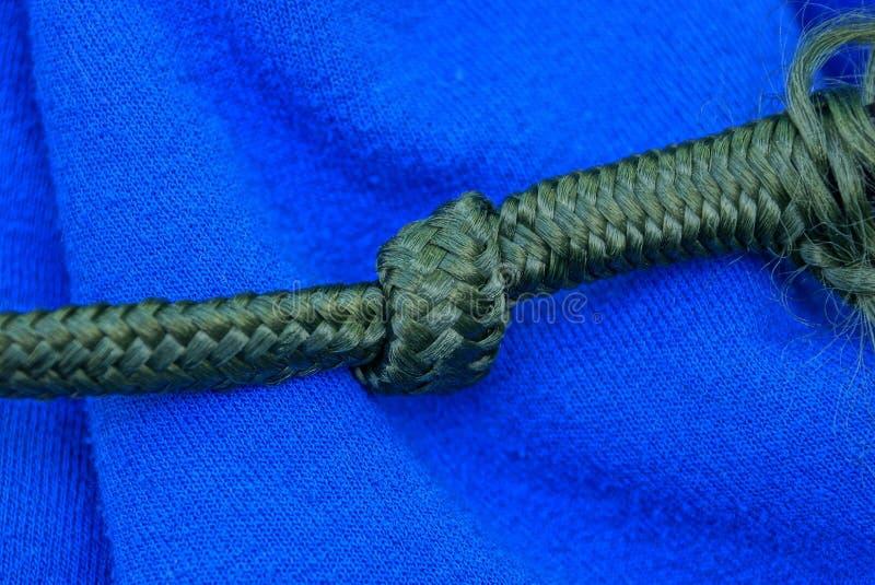 Groen kant met een knoop op de blauwe stof van kleren royalty-vrije stock fotografie