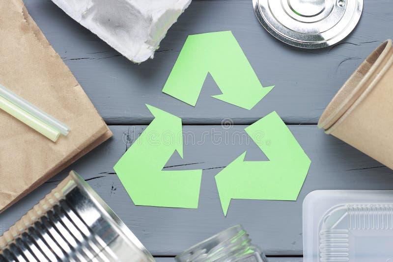 Groen kringloophuisvuilsymbool en plastiek, ijzerhuisvuil op een grijze achtergrond, hoogste mening royalty-vrije stock afbeelding