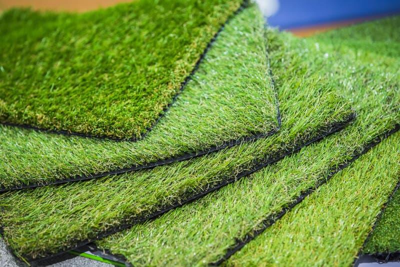 Groen kunstmatig gerold gras Sondes van kunstmatig gras, vloerbedekkingen voor speelplaatsen stock fotografie