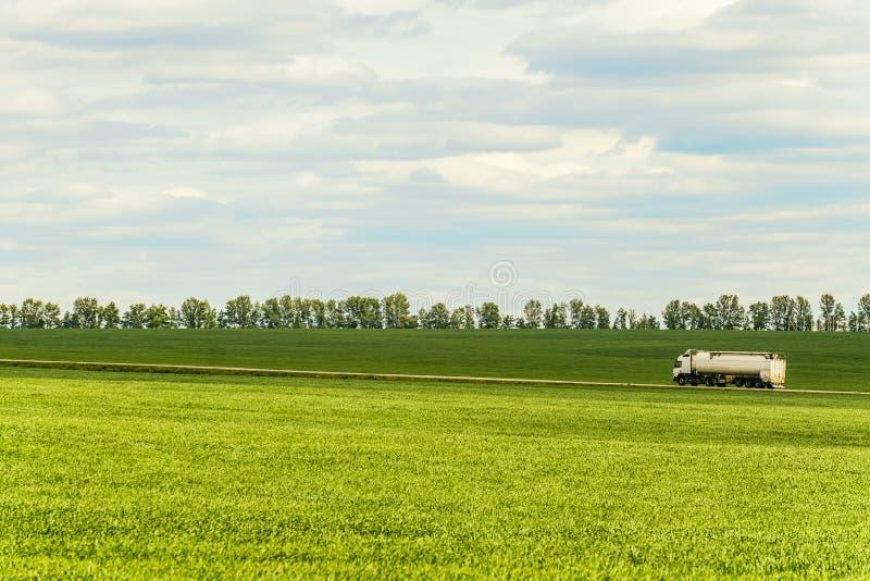 Groen landschap met de witte vrachtwagen van de tankaanhangwagen stock foto's