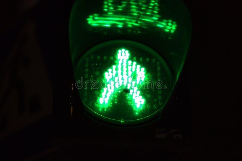Groen licht van verkeerslicht op de voetgangersoversteekplaats in de vorm van een menselijk silhouet Weg die vergunning, signaal  royalty-vrije stock afbeelding