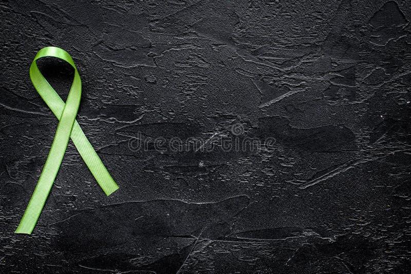Groen lint voor Lyme-ziekte, nierkanker, de voorlichting van de orgaanschenking op zwarte hoogste mening als achtergrond copyspac stock afbeeldingen
