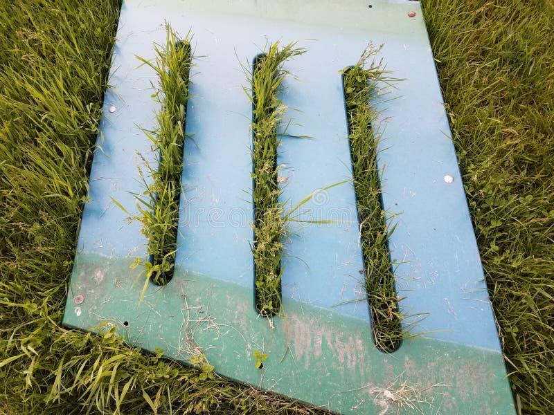 Groen metaal of plastiek met spleten en groen gras of gazon royalty-vrije stock fotografie